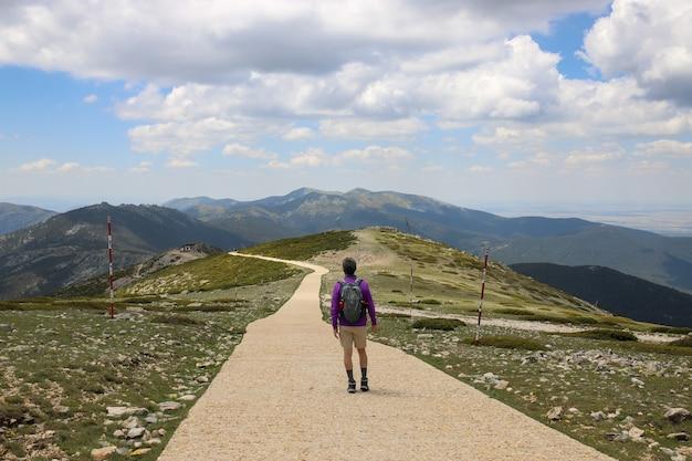 Wanderer mit rucksack zu fuß durch eine straße auf einem begrünten hügel - erfolgskonzept