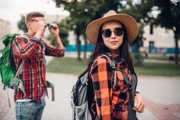 Wanderer mit rucksäcken auf ausflug in die touristenstadt. sommerwandern. wanderabenteuer von jungem mann und frau