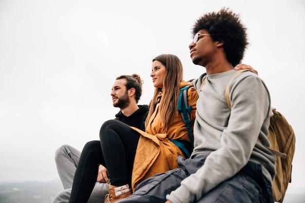 Wanderer mit zwei männern, der mit ihrer freundin sitzt