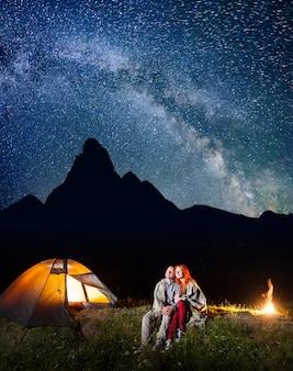 Wanderer nähern sich lagerfeuer und glühendem zelt nachts unter sternen