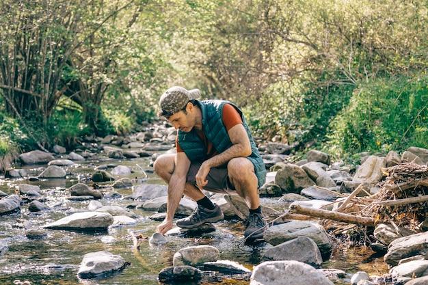 Wanderer sammelt wasser in einem bach mitten im wald
