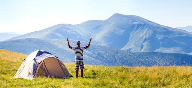 Wanderer trifft guten morgen mit den angehobenen händen, die gerade vom zelt in den bergen ausgestiegen werden.