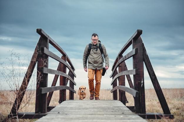 Wanderer und hund auf holzbrücke