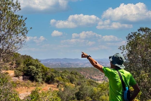 Wanderer zeigt auf die ländliche landschaft an der algarve, portugal.