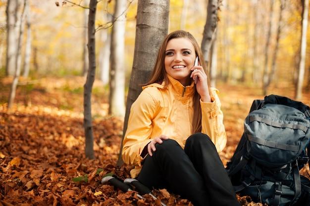 Wandererfrau, die auf mobiltelefon ruht und spricht