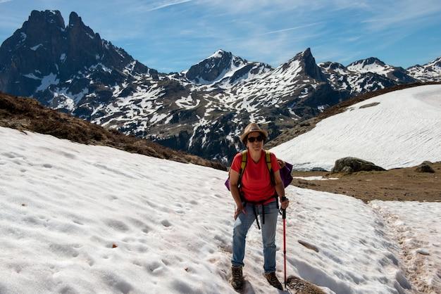 Wandererfrau, die in den schnee, in den französischen pyrenäen-bergen geht