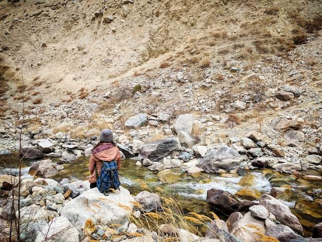 Wandererfrau mit dem rucksack, der auf dem felsen sitzt