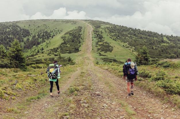 Wanderergruppe wit.ackpacks wandert auf einem weg zu einem bergkamm