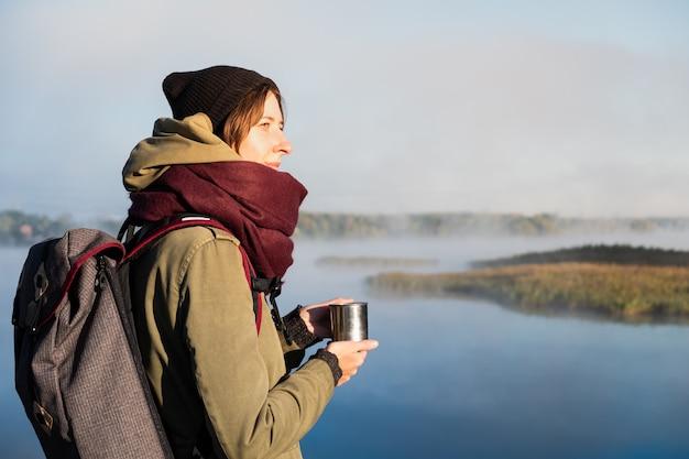 Wandererin genießt schöne naturlandschaft mit einer tasse heißem getränk. junge frau, die kaffee hat und herrlichen fluss bewundert, der im nebel bedeckt ist.