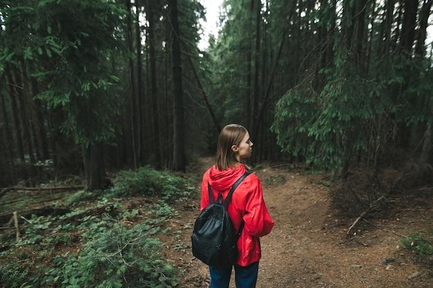 Wandererin in roter jacke steht im wald und schaut weg