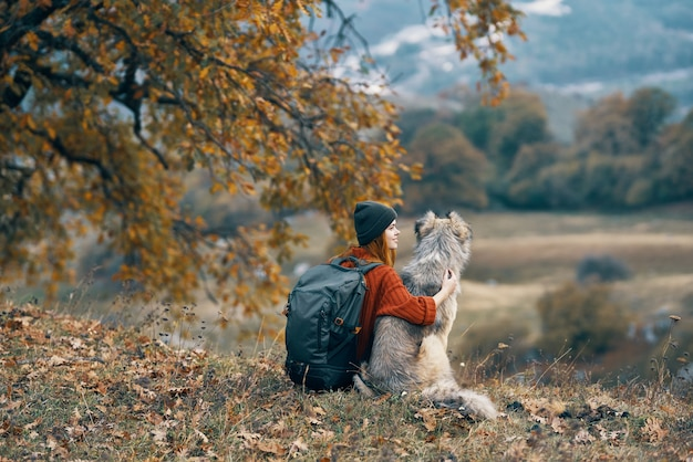 Wandererin mit rucksack neben einem hund bewundert die natur des berges