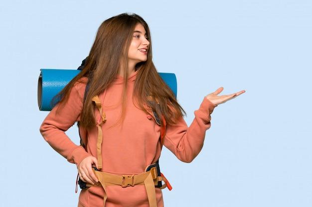 Wanderermädchen, das copyspace eingebildet auf der palme hält, um eine anzeige an auf blau einzufügen