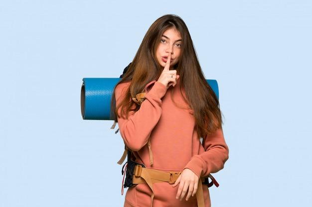 Wanderermädchen, das ein zeichen der ruhegeste finger in mund auf blauen hintergrund setzt zeigt