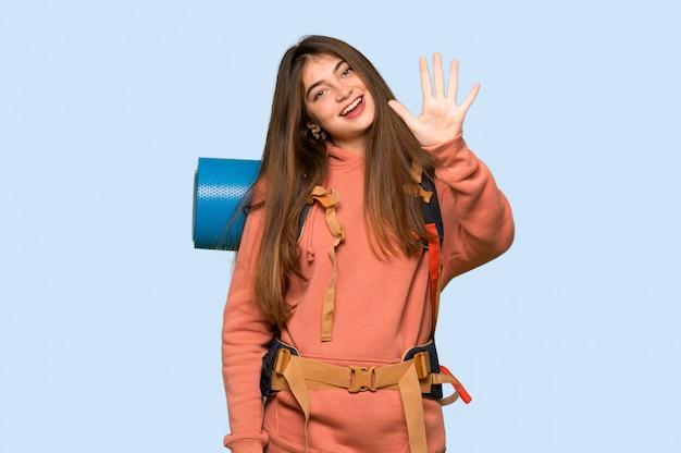 Wanderermädchen, das fünf mit den fingern ein auf blau zählt