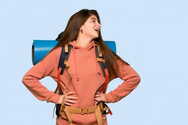 Wanderermädchen, das mit den armen an der hüfte aufwirft und an auf blau lacht