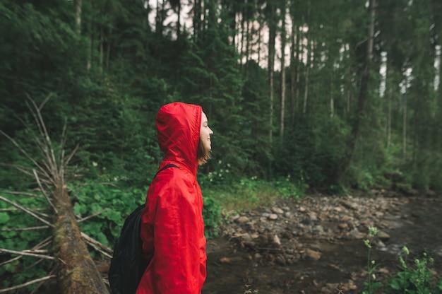 Wanderermädchen in einem roten regenmantel geht in den wald