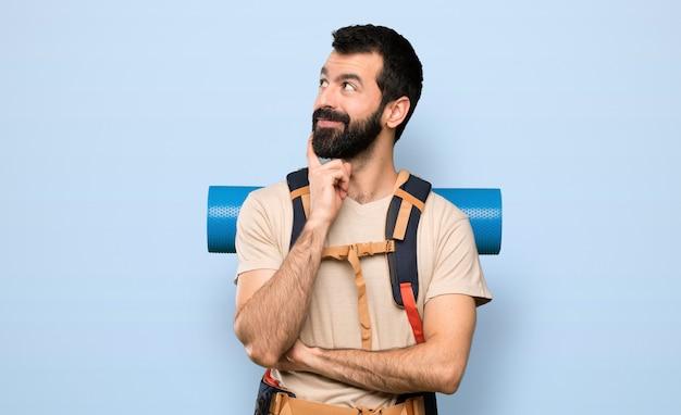 Wanderermann, der eine idee beim oben schauen über lokalisiertem blauem hintergrund denkt