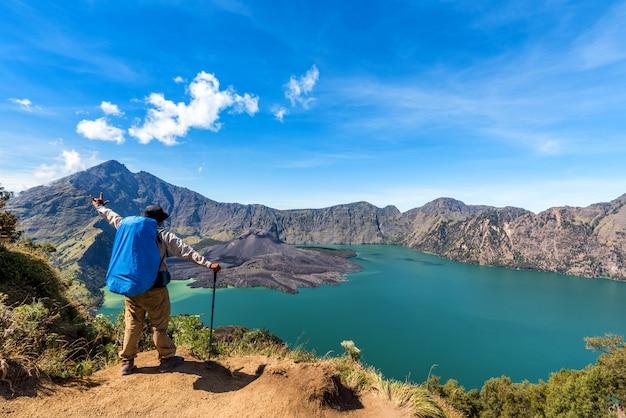 Wanderermann mit der ausgebreiteten hand des rucksacks, genießen und glücklich mit aktivem vulkan baru jari