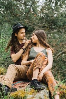 Wandererpaare in der liebe, die in der natur sitzt