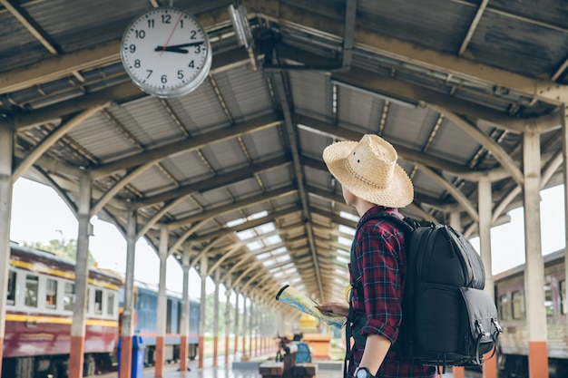 Wandererstand unter uhr im bahnstationstouristen-reisefeiertag reisekonzept mannreisen