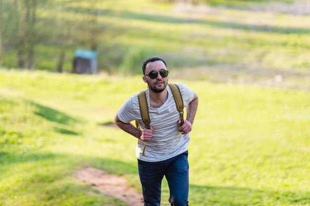 Wandermannporträt mit rucksack, der in der natur geht