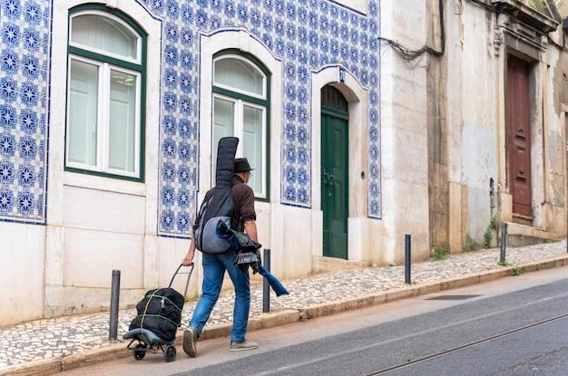 Wandermusiker mit gitarre auf dem rücken zu fuß in den straßen von lissabon portugal