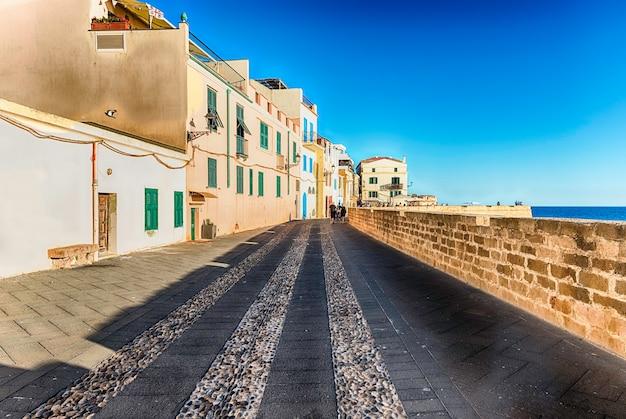 Wandern bei sonnenuntergang auf den historischen stadtmauern, einer der wichtigsten sehenswürdigkeiten in alghero, dem berühmten zentrum und ferienort im nordwesten sardiniens, italien