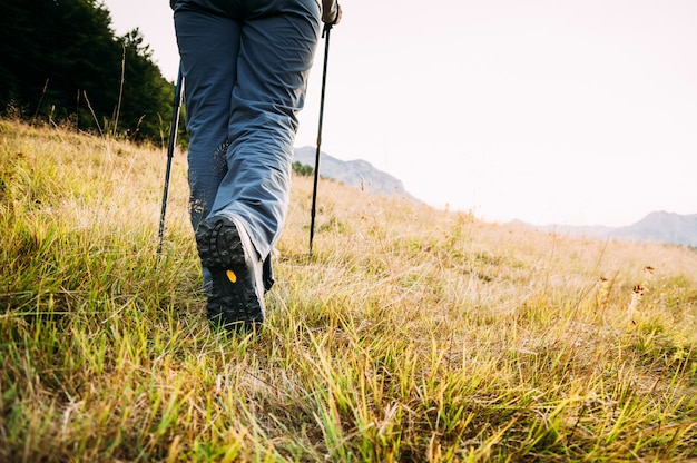 Wandern der beine, die auf bergspitze gehen
