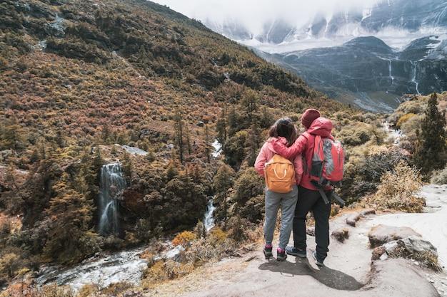 Wandern des jungen paarreisenden, der schöne landschaft yading-naturreservat betrachtet