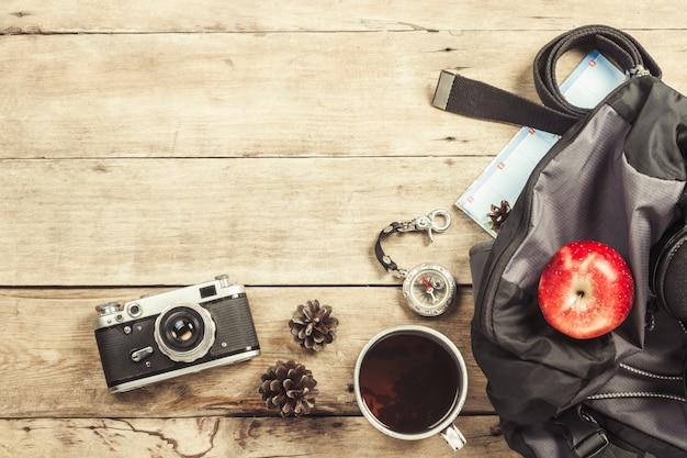 Wandern des rucksacks, des kompassses, des gurtes und anderer kampierender ausrüstung auf einer holzoberfläche. das konzept des wanderns in den bergen oder im wald, tourismus, zeltruhe, lager. flachgelegt, draufsicht.
