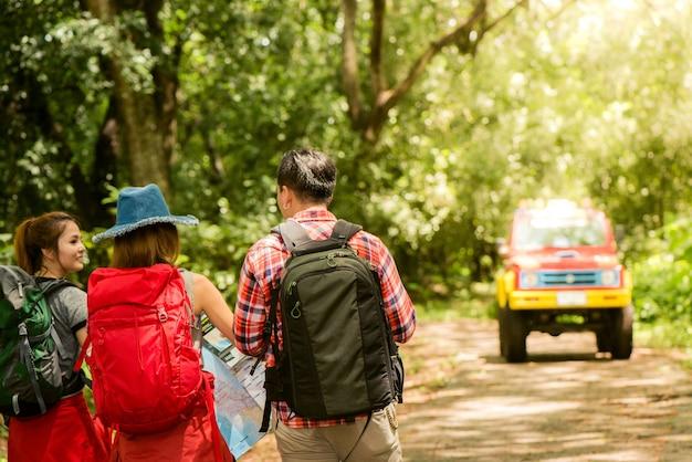 Wandern - wanderer auf der karte. paar oder freunde navigieren zusammen lächelnd glücklich während camping reisen wanderung im freien im wald. junge gemischte rasse asiatische frau und mann.