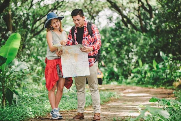Wandern - wanderer, die karte betrachten. die paare oder freunde, die zusammen glücklich lächelnd während der kampierenden reise wandern, wandern draußen in wald. asiatische frau und mann der jungen mischrasse.