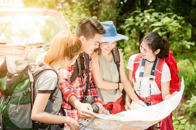 Wandern - wanderer, die karte betrachten. paare oder freunde, die zusammen glücklich lächelnd während der camping-spielraumwanderung draußen im wald navigieren. asiatische frau und mann der jungen mischrasse. wandern reisekonzept.