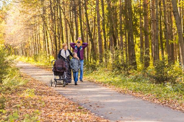 Wandernde familie mit zwei kindern im herbstlichen park.
