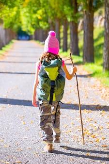 Wanderndes kindermädchen mit hinterer ansicht des spazierstockes und des rucksacks