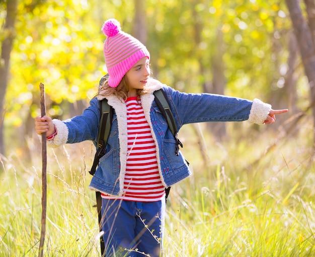 Wanderndes kindermädchen mit rucksack finger im autum wald zeigend