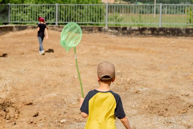 Wanderndes land des kleinen jungen mit einem netz im sommer. hellgrünes netz in den händen eines kindes. sommerstimmung. gelbes t-shirt. glückliche kindheit in den sommerferien