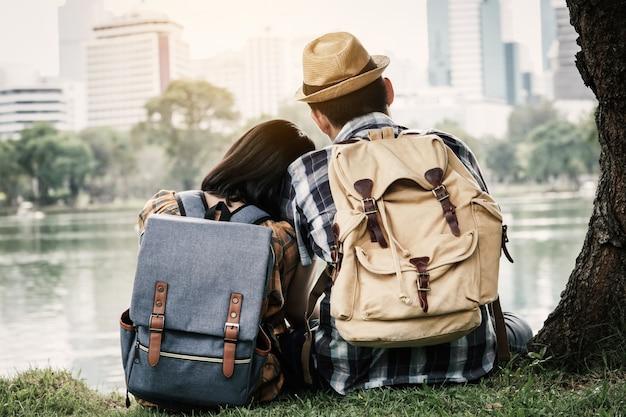 Wanderndes sitzen der hippie-paare unter dem baum auf park, reise am feiertagskonzept.