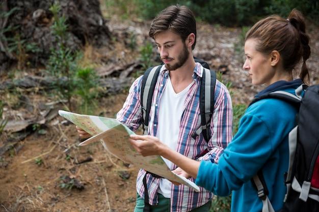 Wanderpaar, das karte und kompass betrachtet