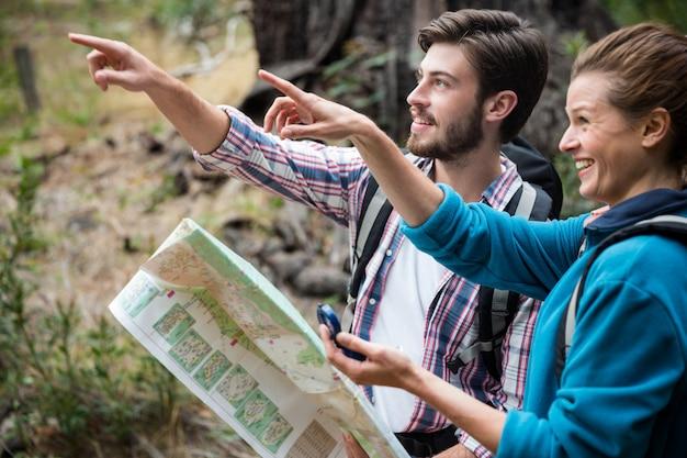 Wanderpaar hält karte und zeigt richtung