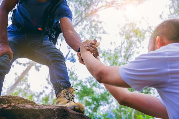 Wanderreisender mit hand, die sich gegenseitig helfen, gemeinsam einen berggipfel zu erklimmen