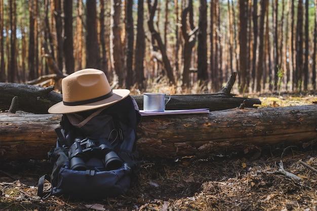Wanderrucksack, hut, becher mit heißem tee und karte auf dem hintergrund des waldes. wanderung in den bergen, wald.
