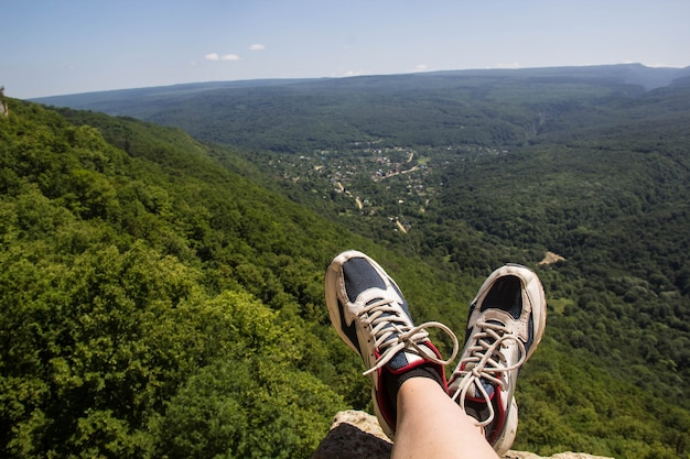Wanderschuhe, die spaß haben und einen atemberaubenden blick auf die berge genießen. lifestyle- und reisekonzept.
