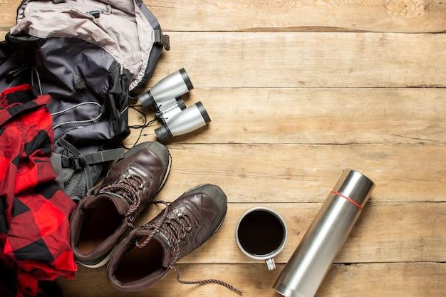 Wanderschuhe, fernglas, hemd, thermoskanne, rucksack auf einem hölzernen hintergrund. das konzept von wandern, tourismus, camp, bergen, wald. banner. flache lage, draufsicht
