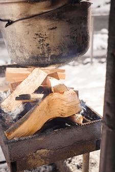 Wandertopf im lagerfeuer. kochen im winter in der nähe des flusses.