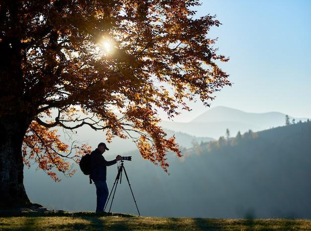 Wandertouristenmann mit kamera auf grasigem tal auf hintergrund der berglandschaft unter großem baum.