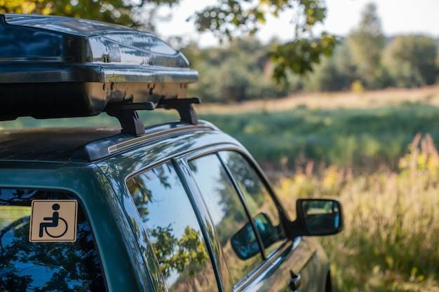 Wanderung mit dem auto für rollstuhlfahrer. reisekonzept für alle. ein auto mit einem autoträger auf dem dach steht im sommer auf einer lichtung