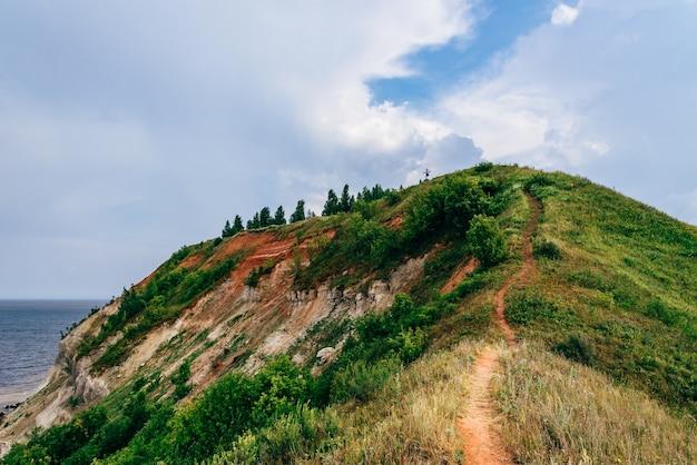 Wanderweg am berghang am wolkigen sommertag