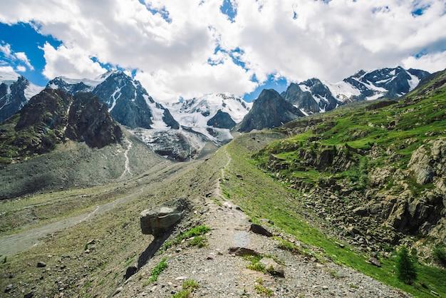 Wanderweg führt zu riesigen schneebedeckten bergen im sonnigen tag. wundervoller gletscher im sonnenlicht. wasserströme am berg. reiche vegetation des hochlands. atmosphärische sonnige minimalistenlandschaft der natur.