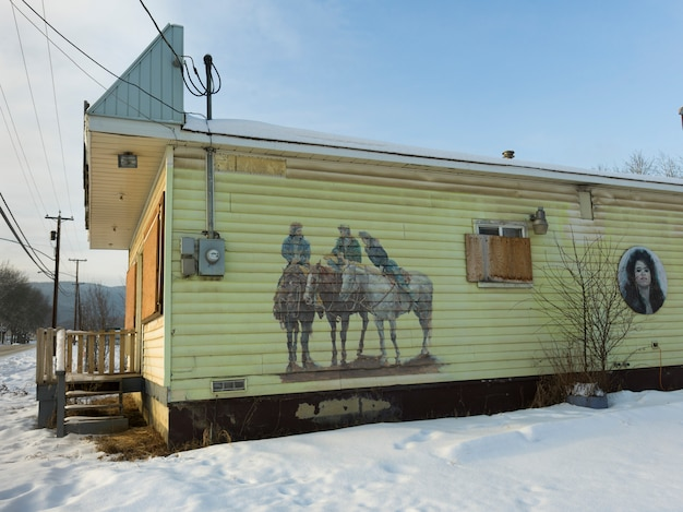 Wandgemälde von cowboys auf wand eines gebäudes im schnee, chetwynd, britisch-columbia, kanada